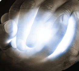 male hands clasped around a bright blue light
